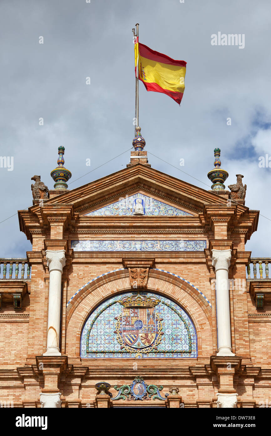 Spanish flag and crest on an apex of pavilion on Plaza de Espana in Seville, Spain. - Stock Image