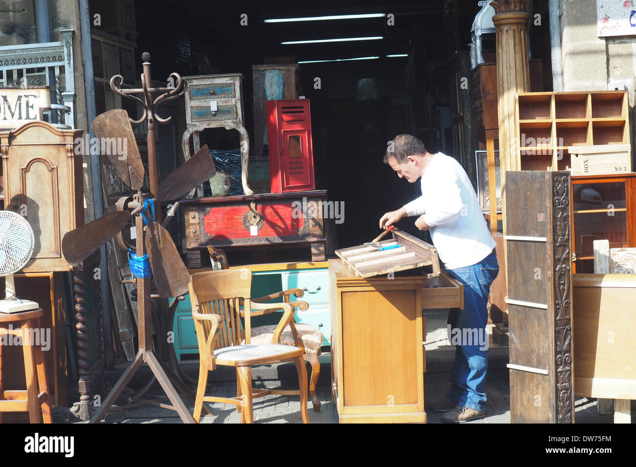Vendor working on old drawers in front of an old furniture store in Jaffa, Yafo - Stock Image