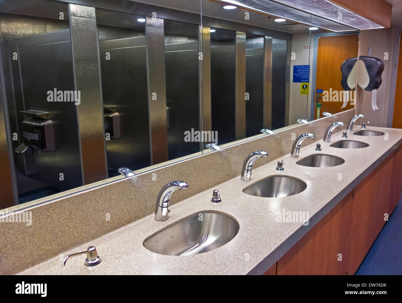 Row of sinks and metal stalls reflecting in the mirror in public washroom on BC ferry boat.  Automated taps for cleanliness. - Stock Image
