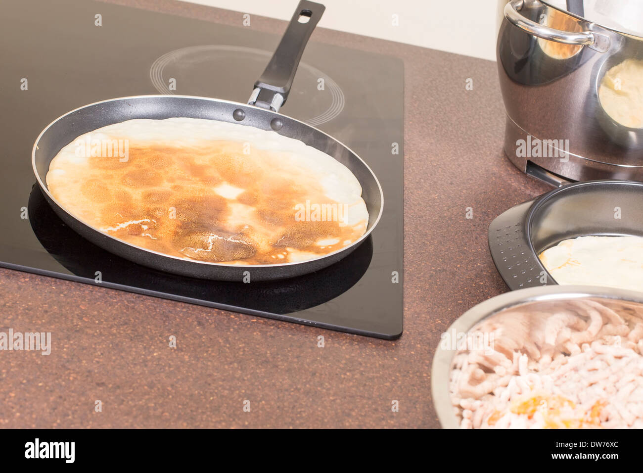 frying of pancakes on ceramic plate - Stock Image