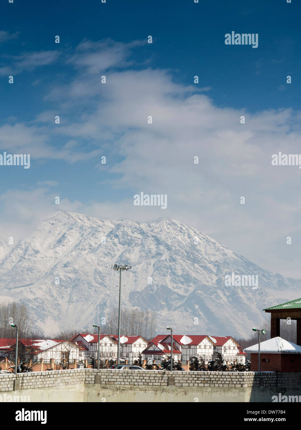 India, Kashmir, Nowgam, Srinagar Railway station, newly built housing below snow clad mountain - Stock Image