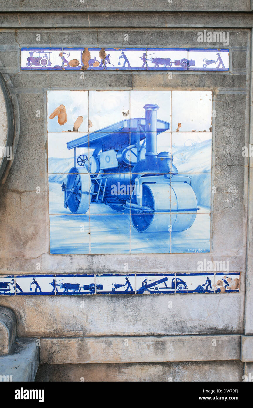 Blue and white tiled panel or azulejos showing a steam road roller Estói, Algarve, Portugal, Europe - Stock Image