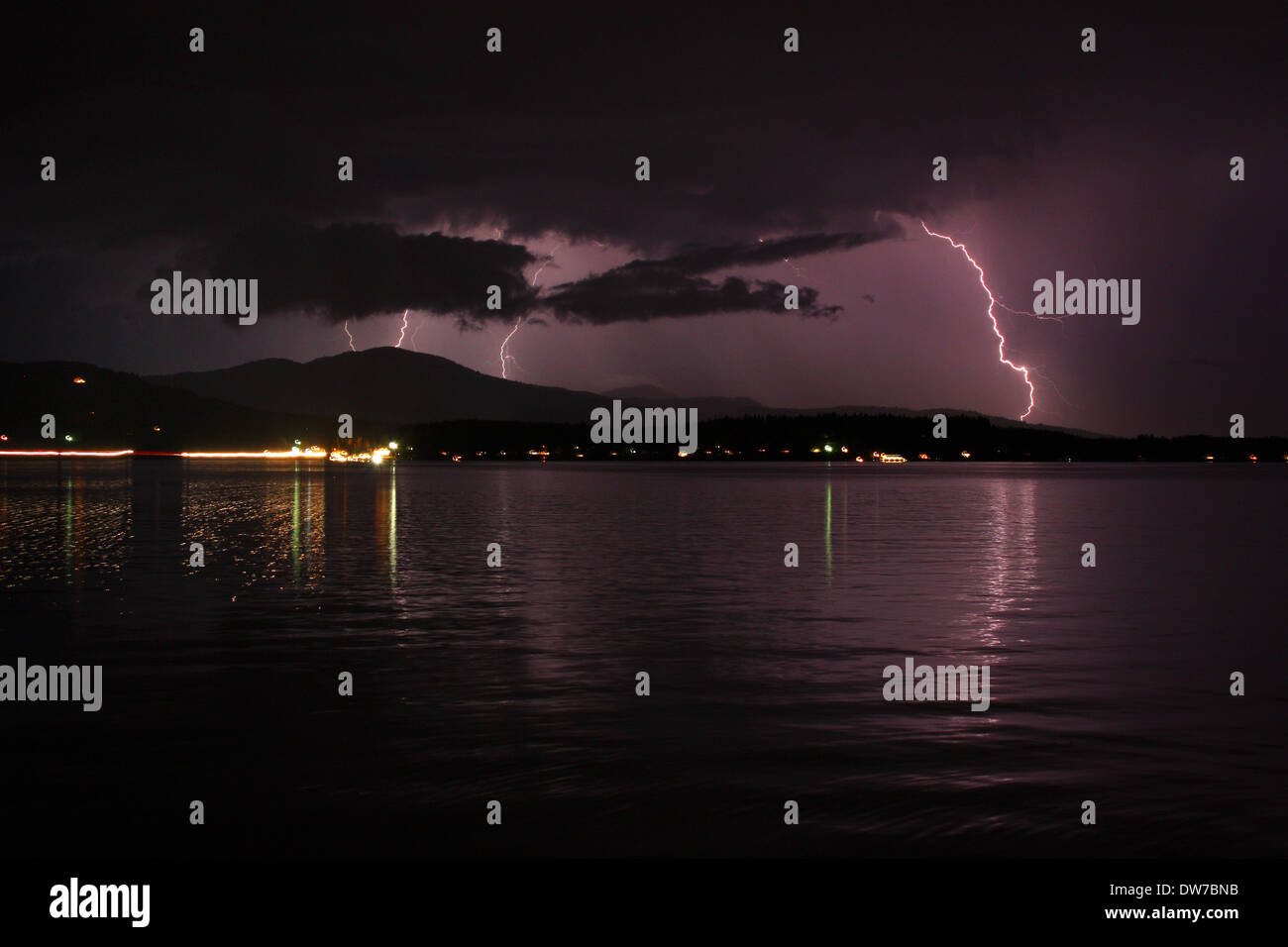 Thunder & lighting storm in the cloudy, purple night sky, reflecting onto the lake water in Sandpoint Idaho. - Stock Image