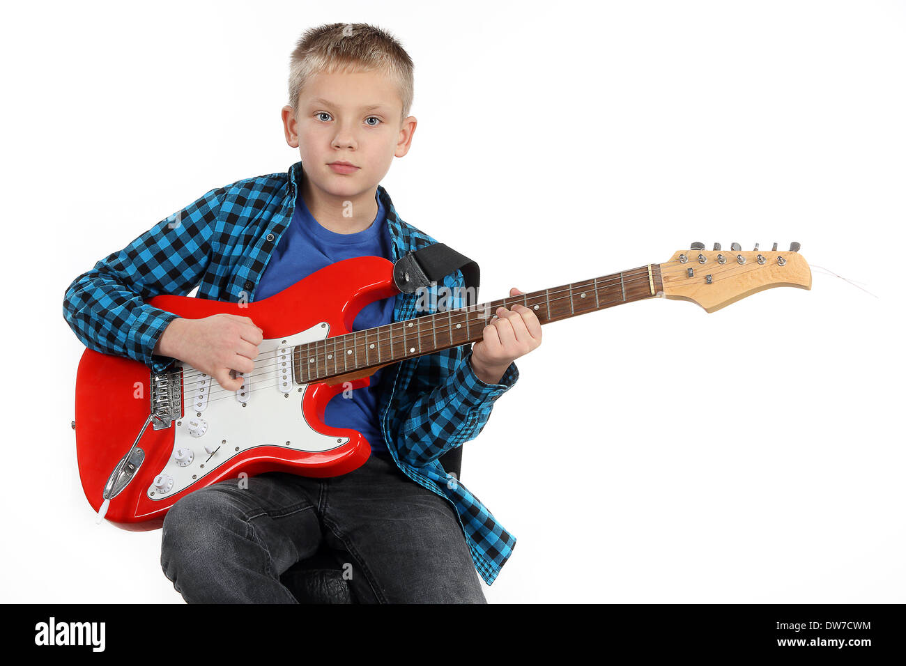 Handsome young boy playing on red electric guitar on white background - Stock Image