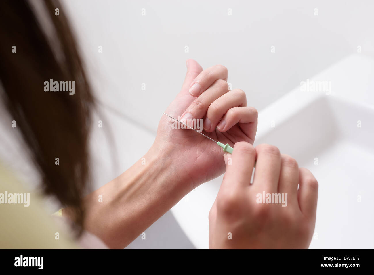 woman using soap to wash her hands with water in a white handbasin - Stock Image