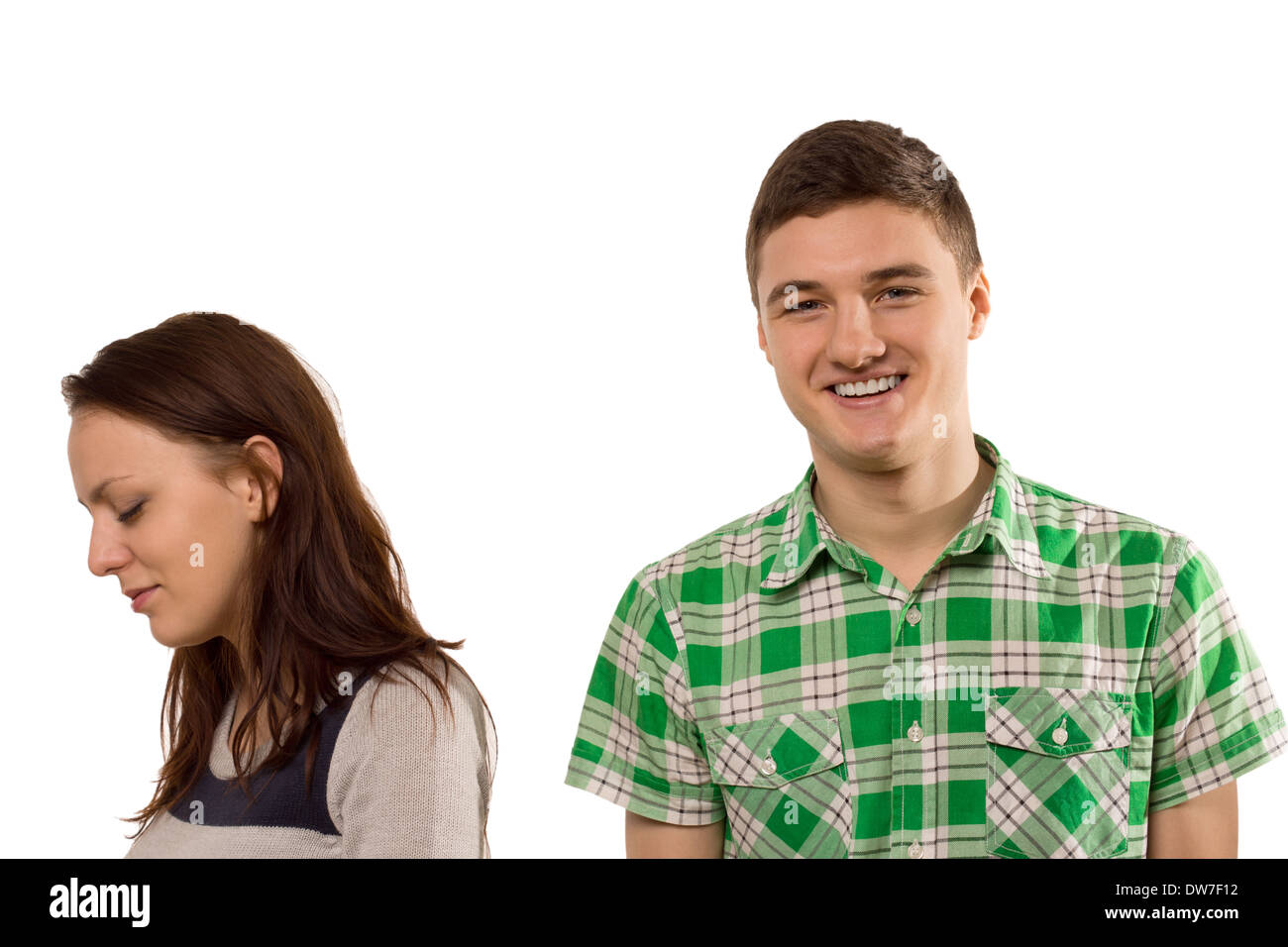 nconsiderate unfeeling handsome young man smiling with pleasure as his girlfriend turns aside in tears upset at his oblivious at - Stock Image