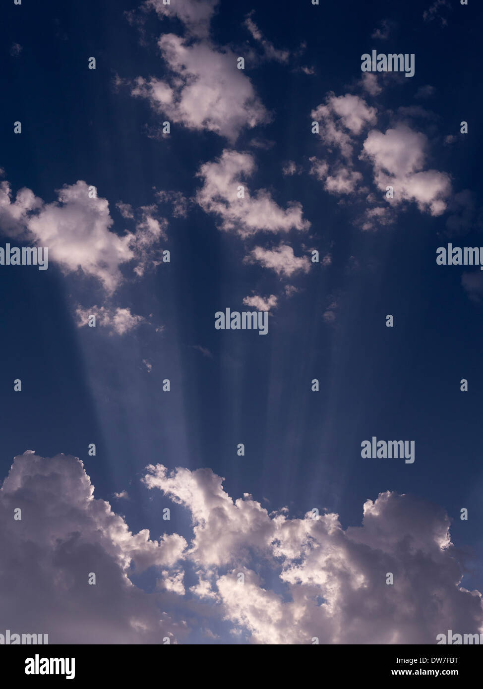 Radiating sunbeams and white clouds against blue sky - Stock Image