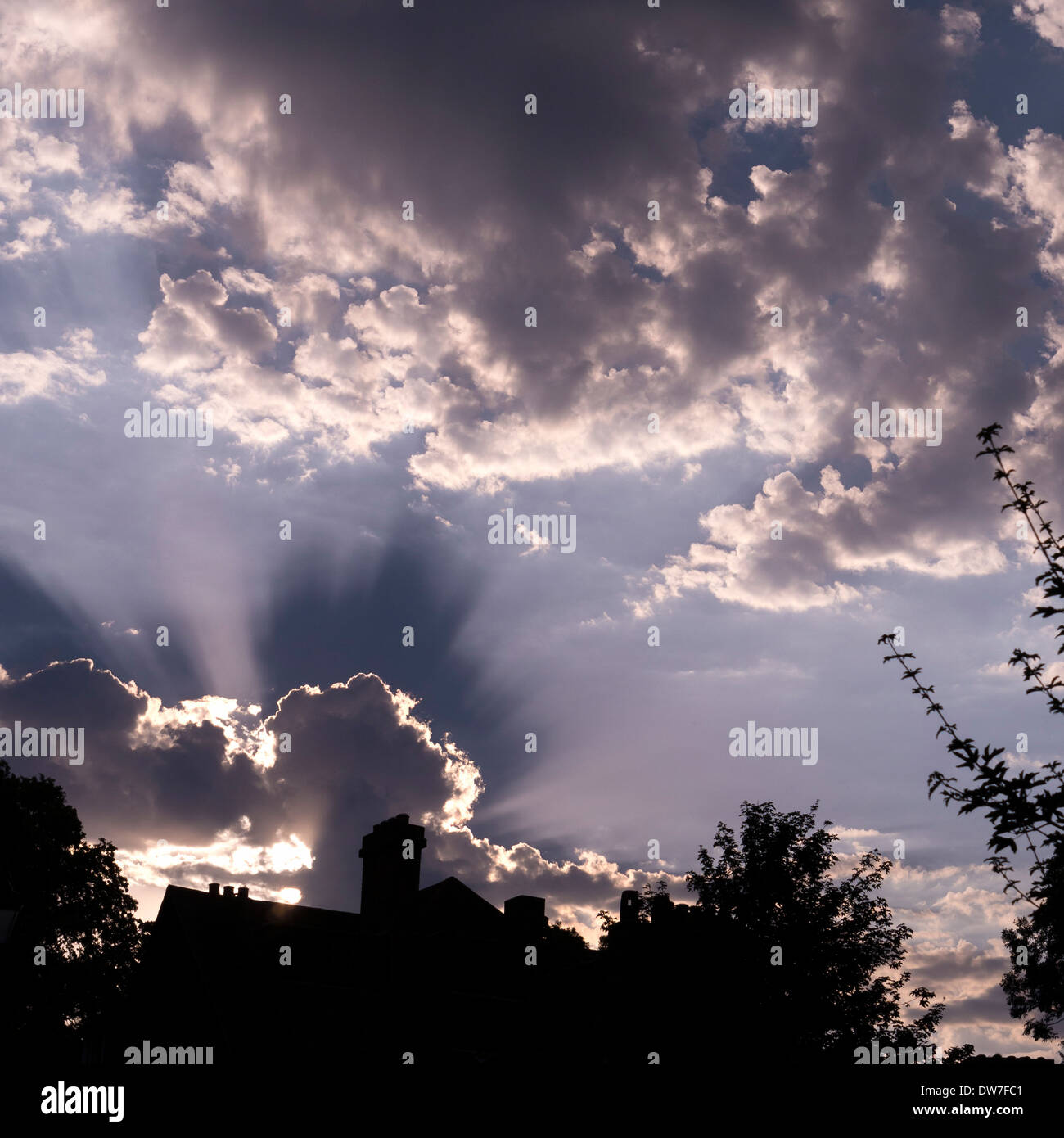 Radiating sun beams and cloud shadows with house silhouette against blue sky - Stock Image