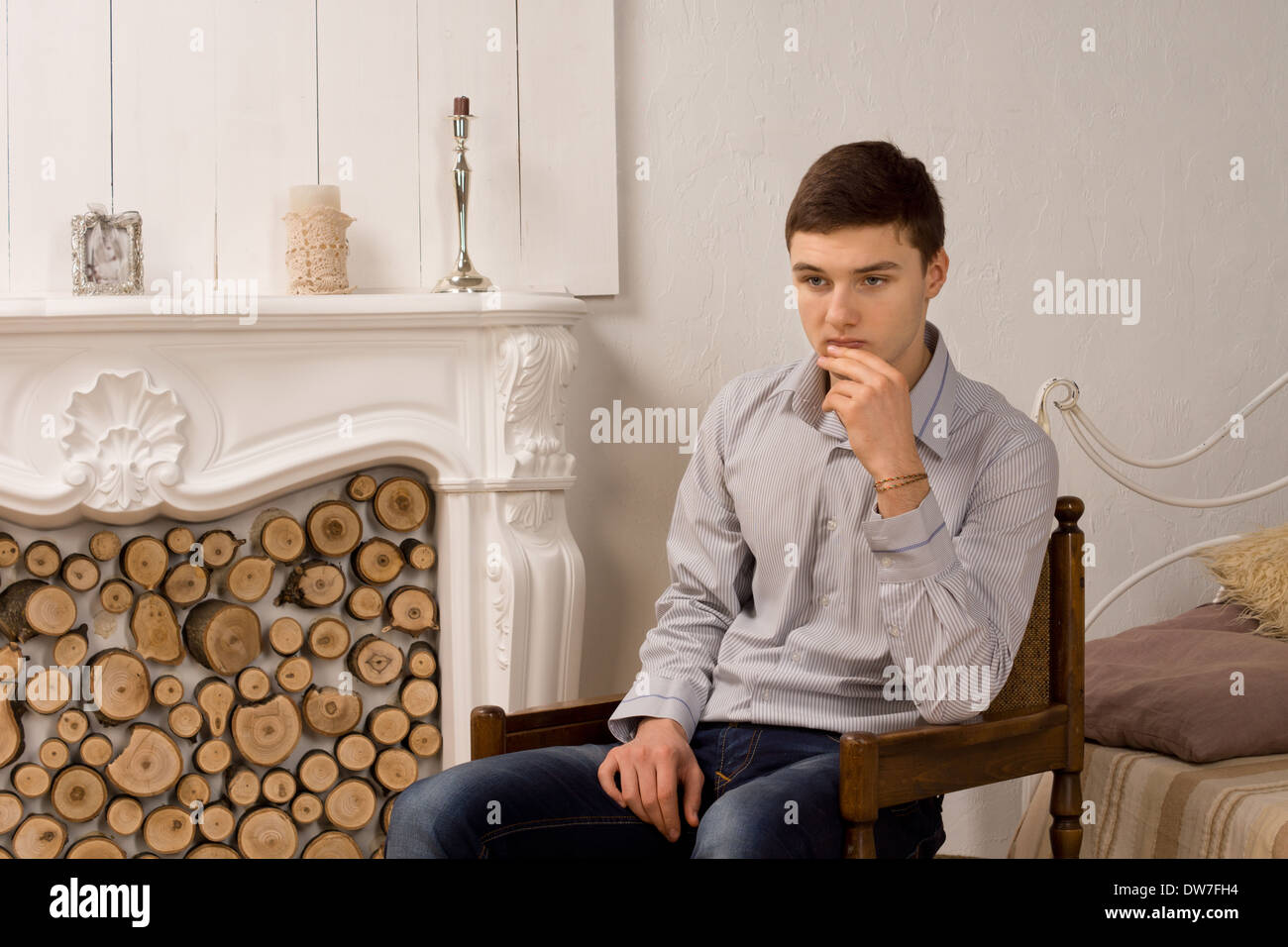 Worried young man deep in thought sitting in a wooden armchair with his hand to his chin staring gloomily at the floor - Stock Image