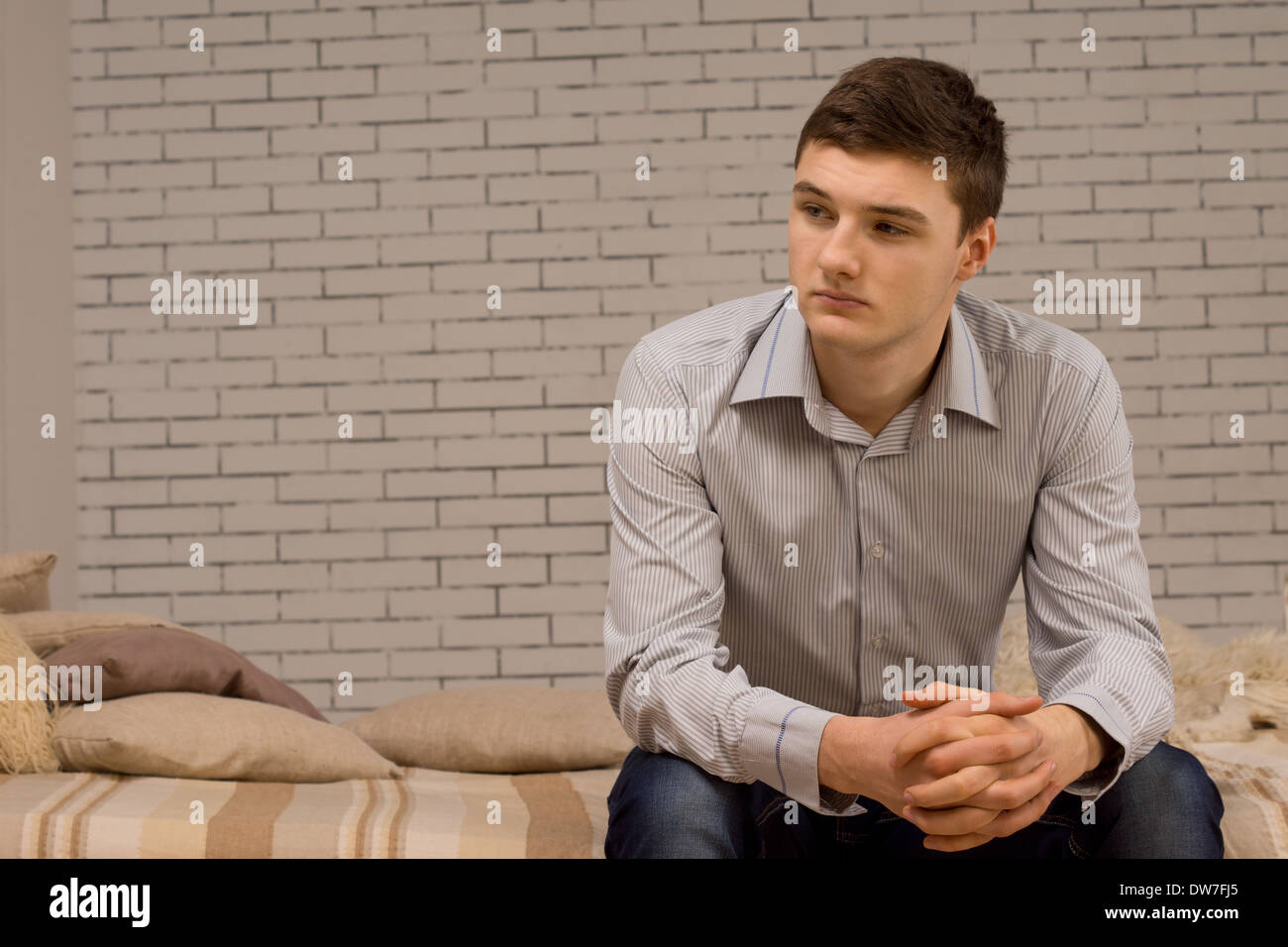 Young man sitting on a sofa thinking - Stock Image