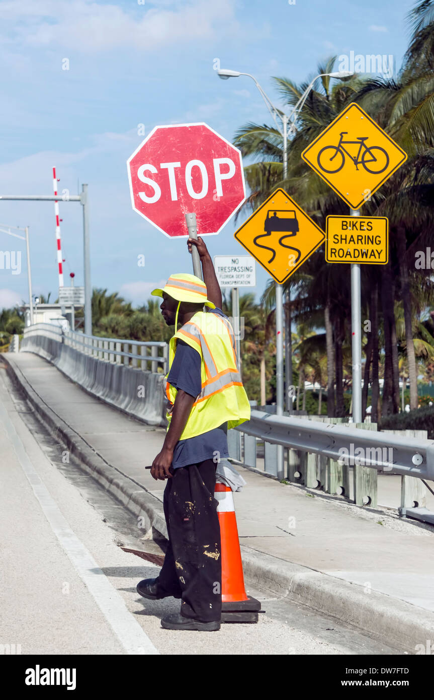 Flagman holding stop sign cont...