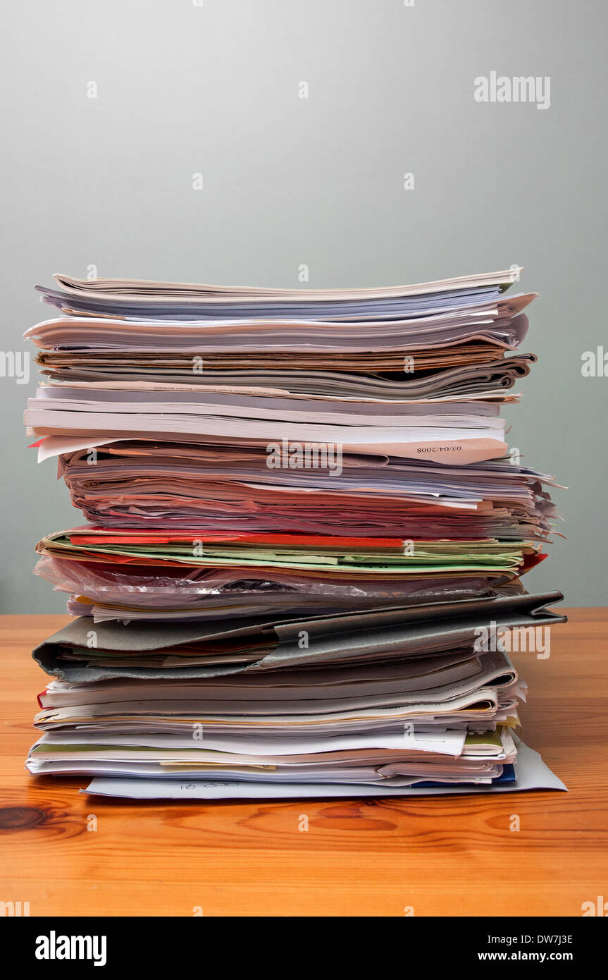 a pile of old office files and paperwork on a desk - Stock Image