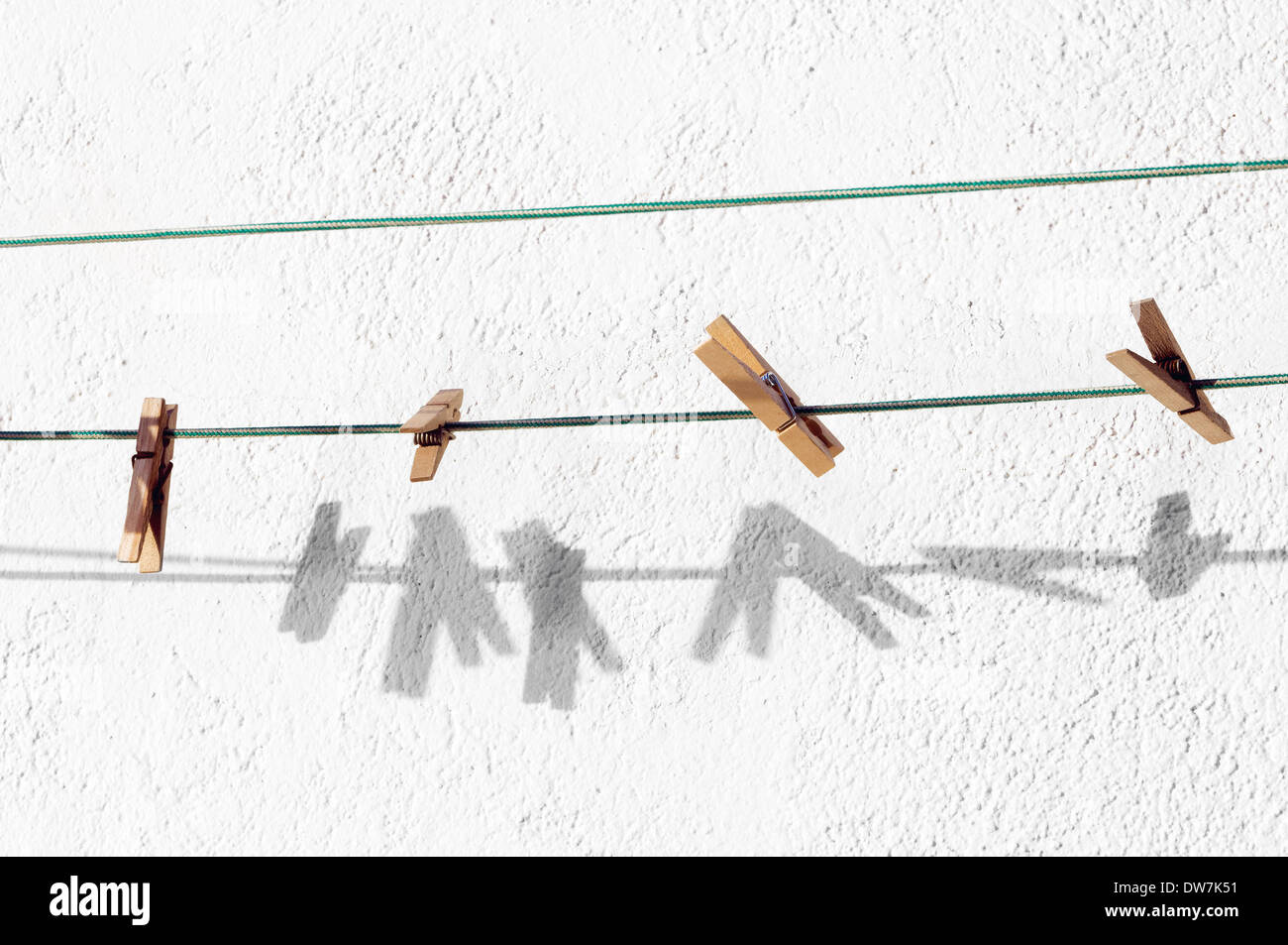 peg for clothes hanging on rope and shadows - Stock Image