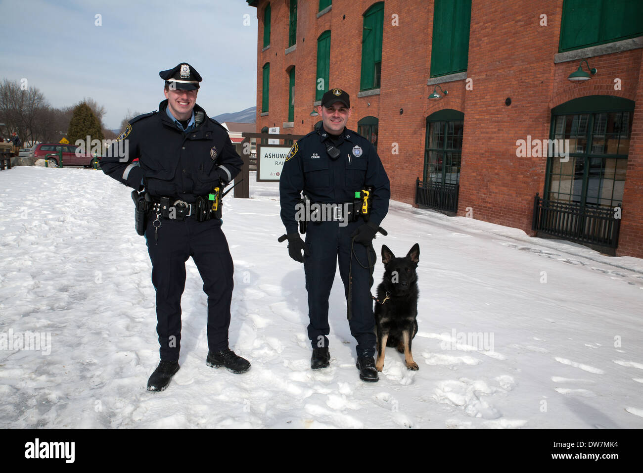 Two human police officers pose with the town's new dog police officer. - Stock Image