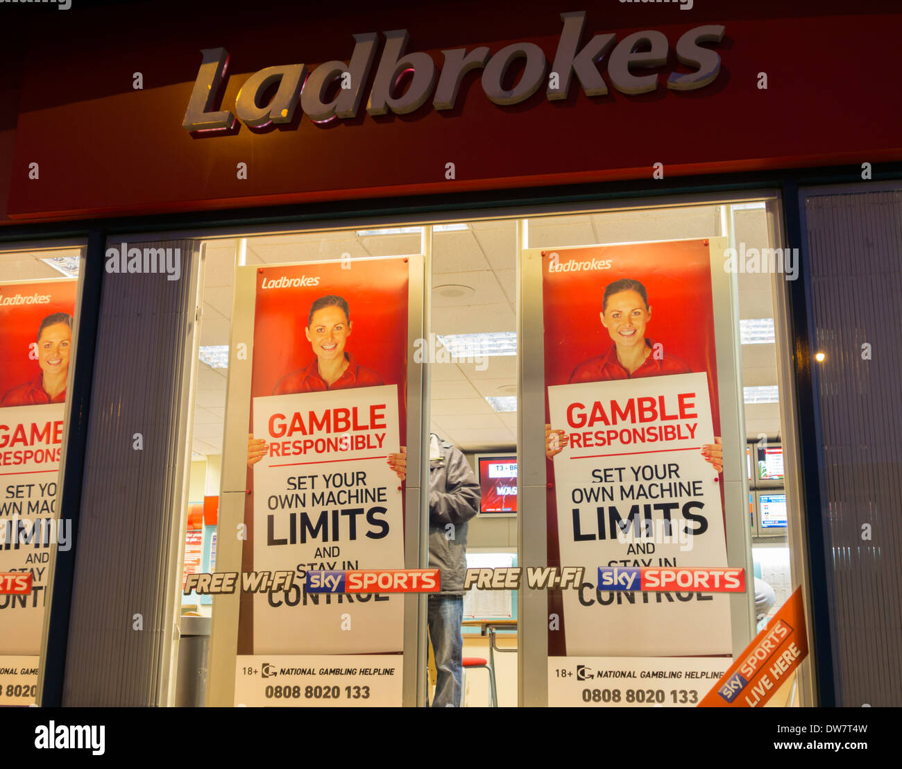 Gamble responsibly posters showing national gambling helpline number in Ladbrokes Bookmakers. - Stock Image