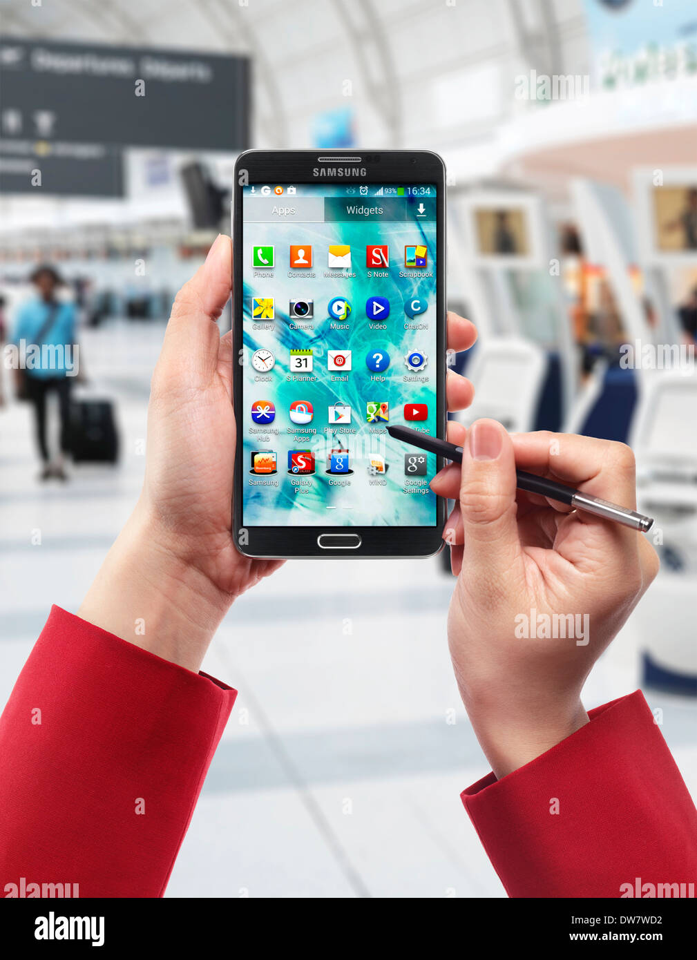 Woman hands with Samsung Galaxy Note III smartphone at airport - Stock Image