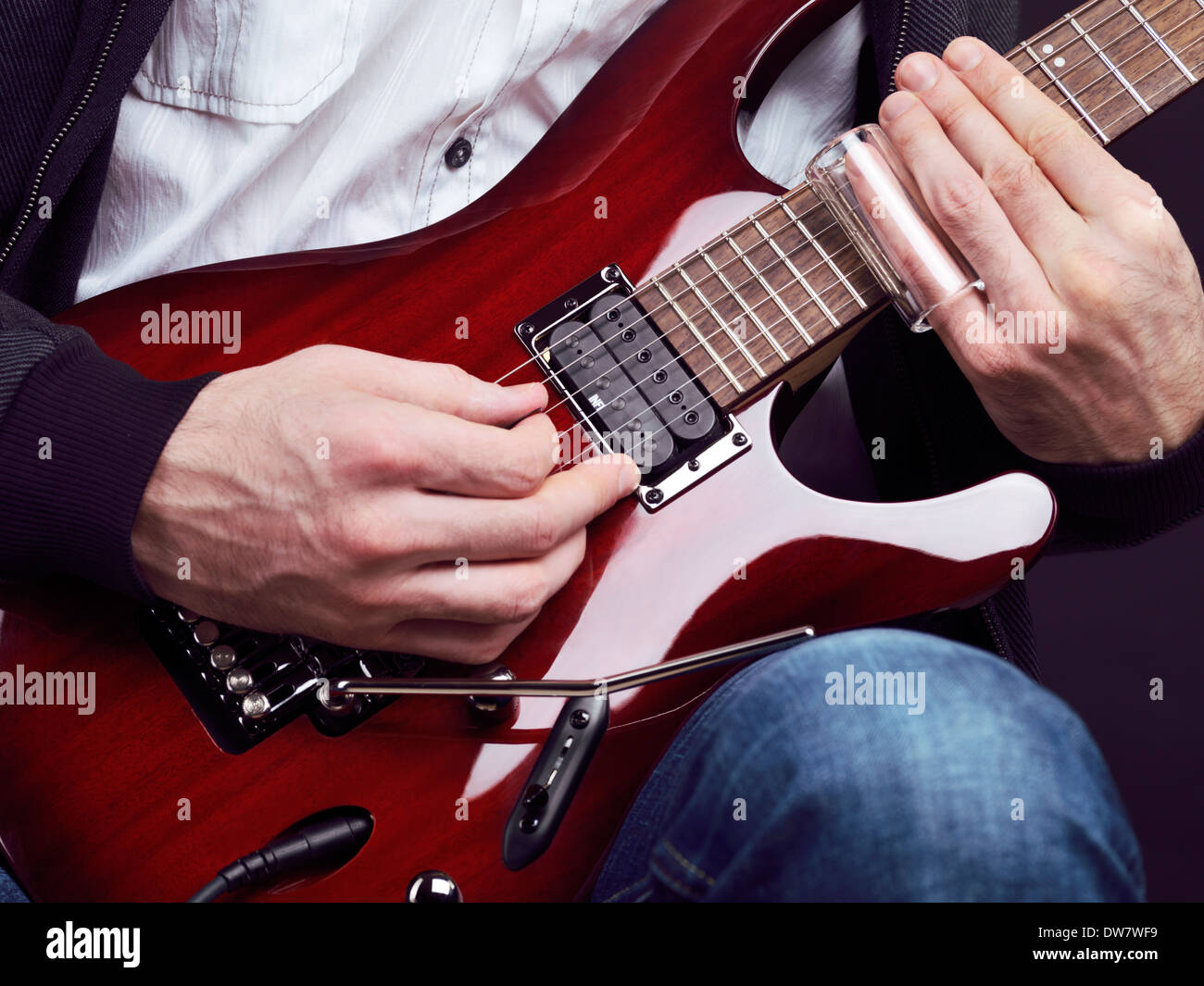 Closeup of man hands playing red electric guitar with a slide - Stock Image
