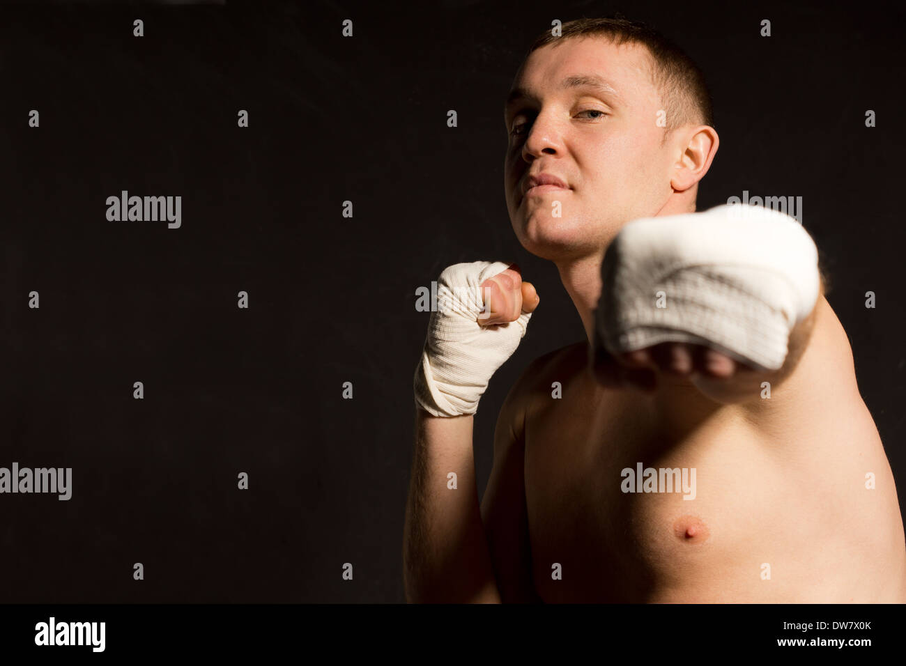Belligerent young boxer throwing a punch - Stock Image