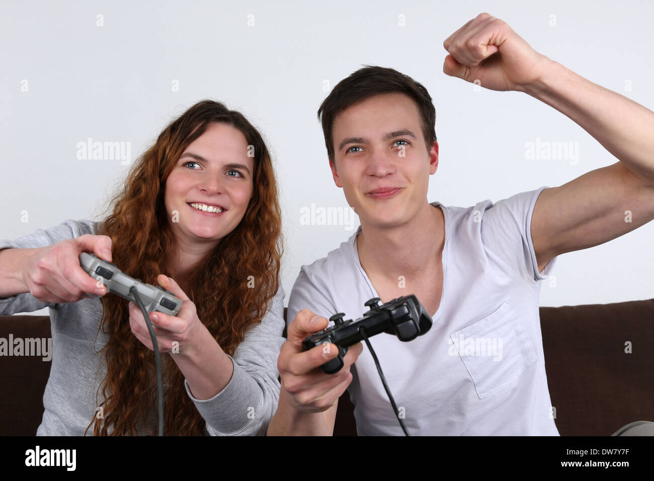 Two young people having fun while playing video games Stock Photo