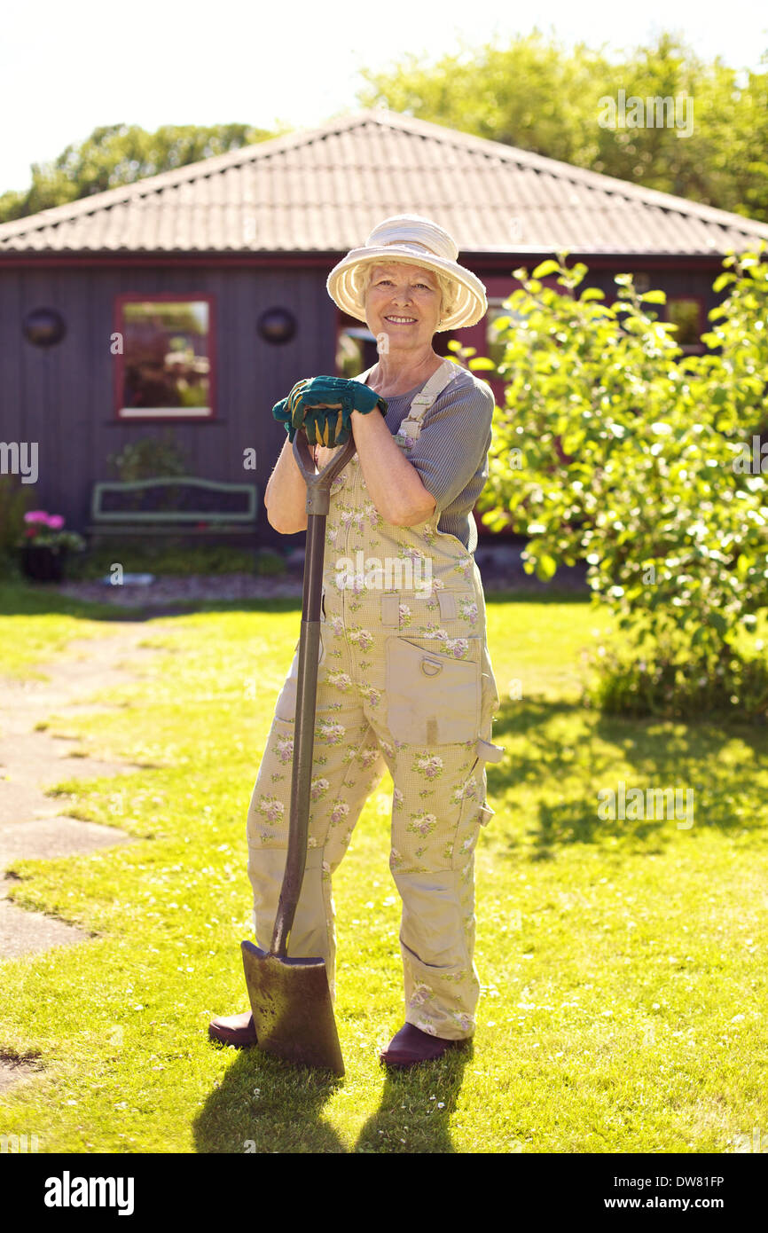 Full length portrait of active senior woman wearing hat with gardening tools smiling outdoors. Elder woman standing - Stock Image