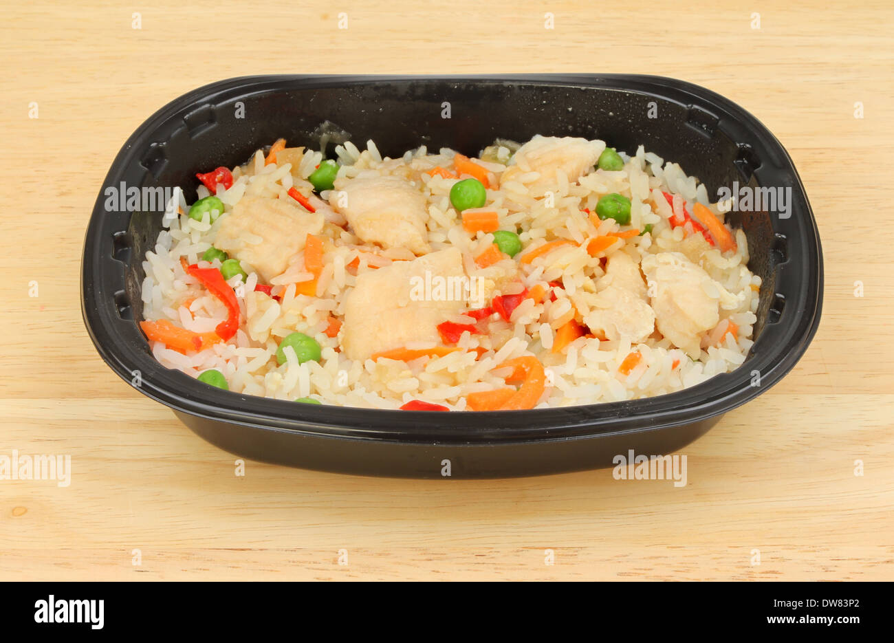 Chinese convenience meal in a plastic tray on a wooden worktop - Stock Image