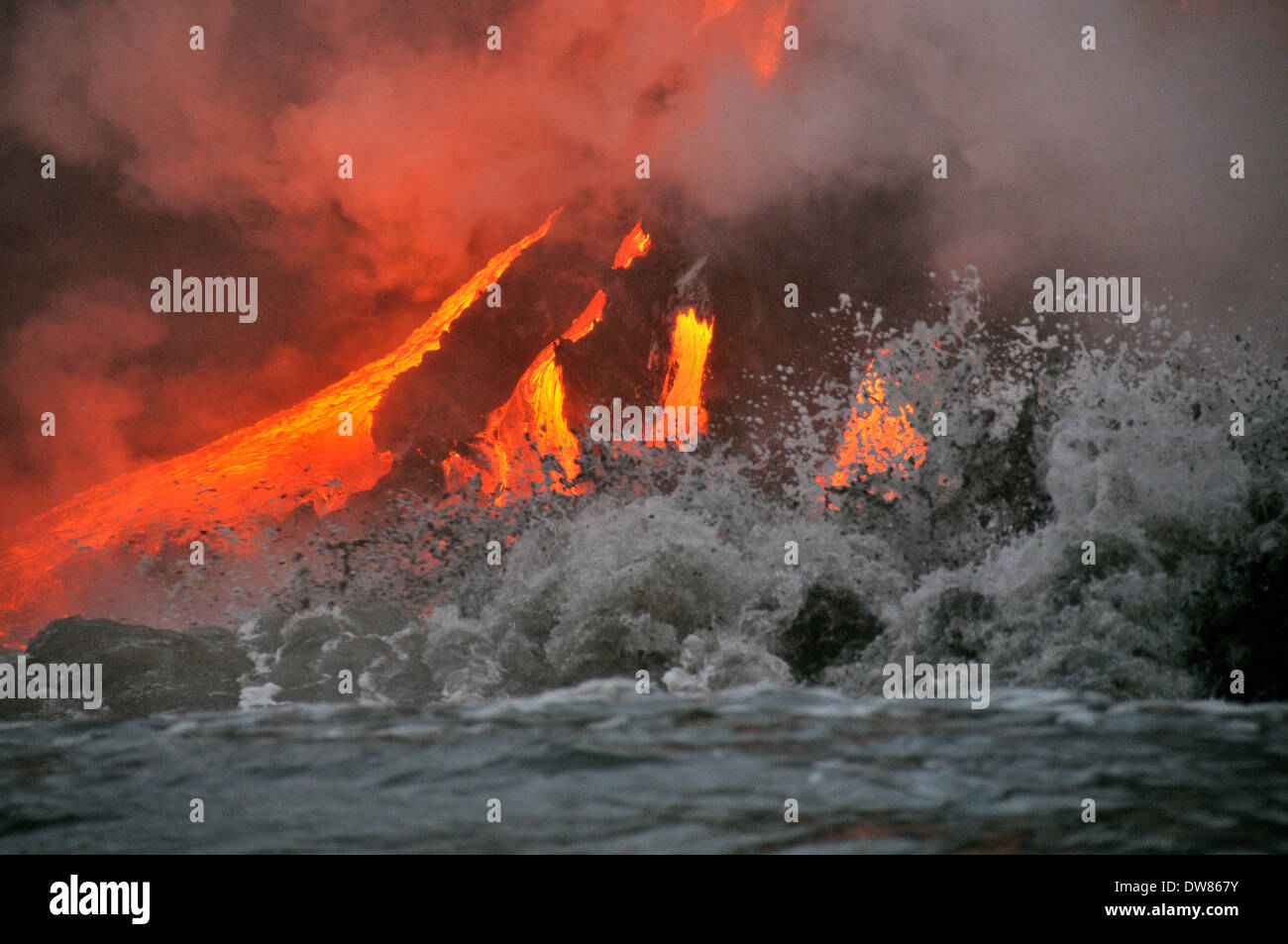 Waves crashing and lava from Kilauea Volcano flowing into the ocean, Hawaii Volcanoes National Park, Big Island, Hawaii, USA - Stock Image