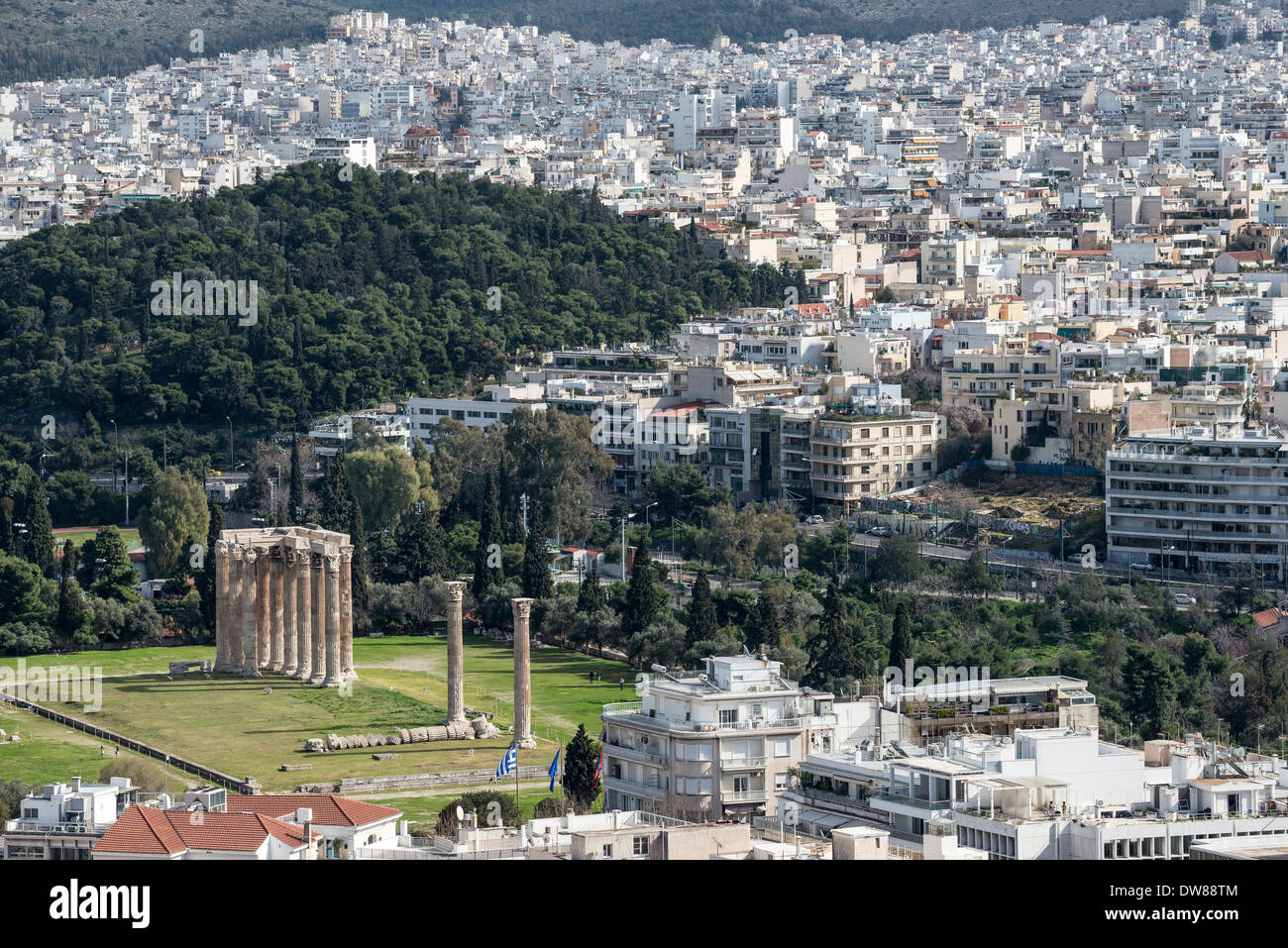 Ancient site of the Temple of Olympian Zeus seen against the modern city skyline of Athens, Greece, - Stock Image
