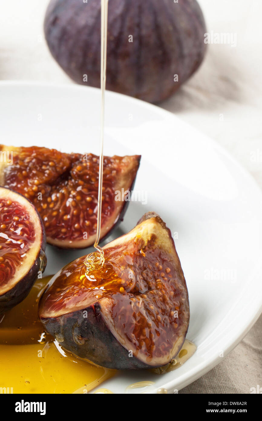 White plate with sliced figs and flowing honey - Stock Image