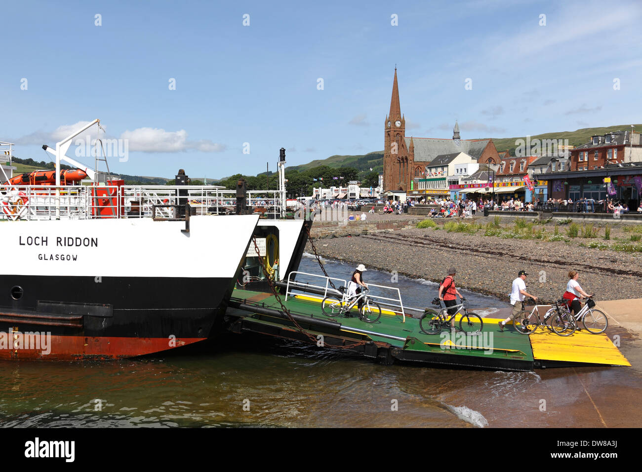 Cyclist leaving a Calmac Ferry after sailing from the Island of Great Cumbrae to Largs, Firth of Clyde, Scotland, UK - Stock Image