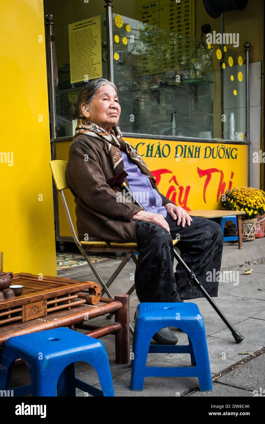 HANOI, VIETNAM- JANUARY 27: An elderly Vietnamese woman sitting on the street in the countries capital city Hanoi Stock Photo