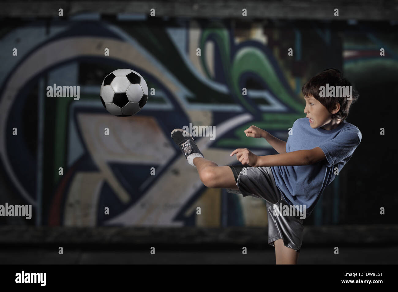 A young boy plays street soccer against a graffiti covered wall - with dramatic lighting and subdued colors - Stock Image