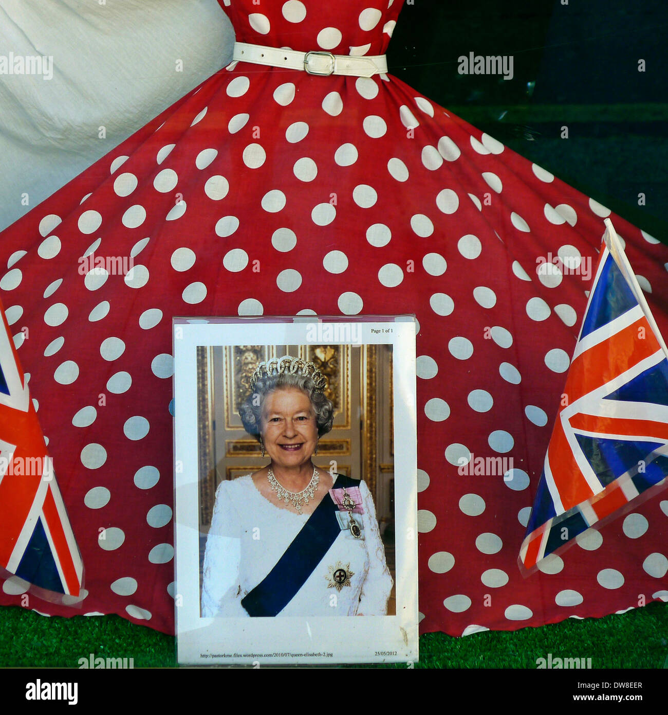 Union flags and photograph of the Queen in font of red spotted dress in shop window - Stock Image
