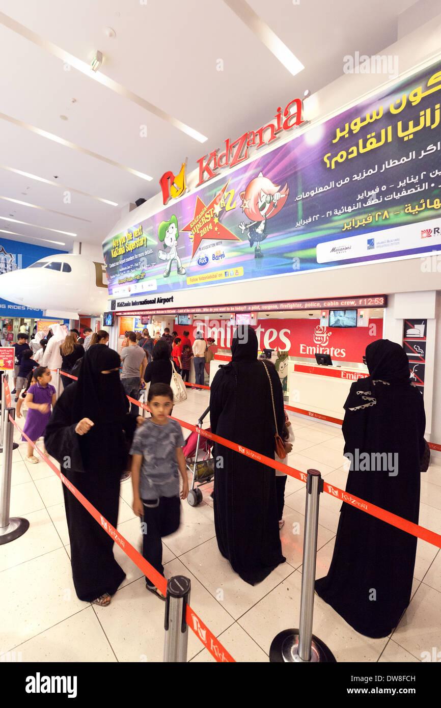Families with children queuing at the entrance to Kidzania childrens area, Dubai Mall, Dubai UAE, United Arab Emirates - Stock Image