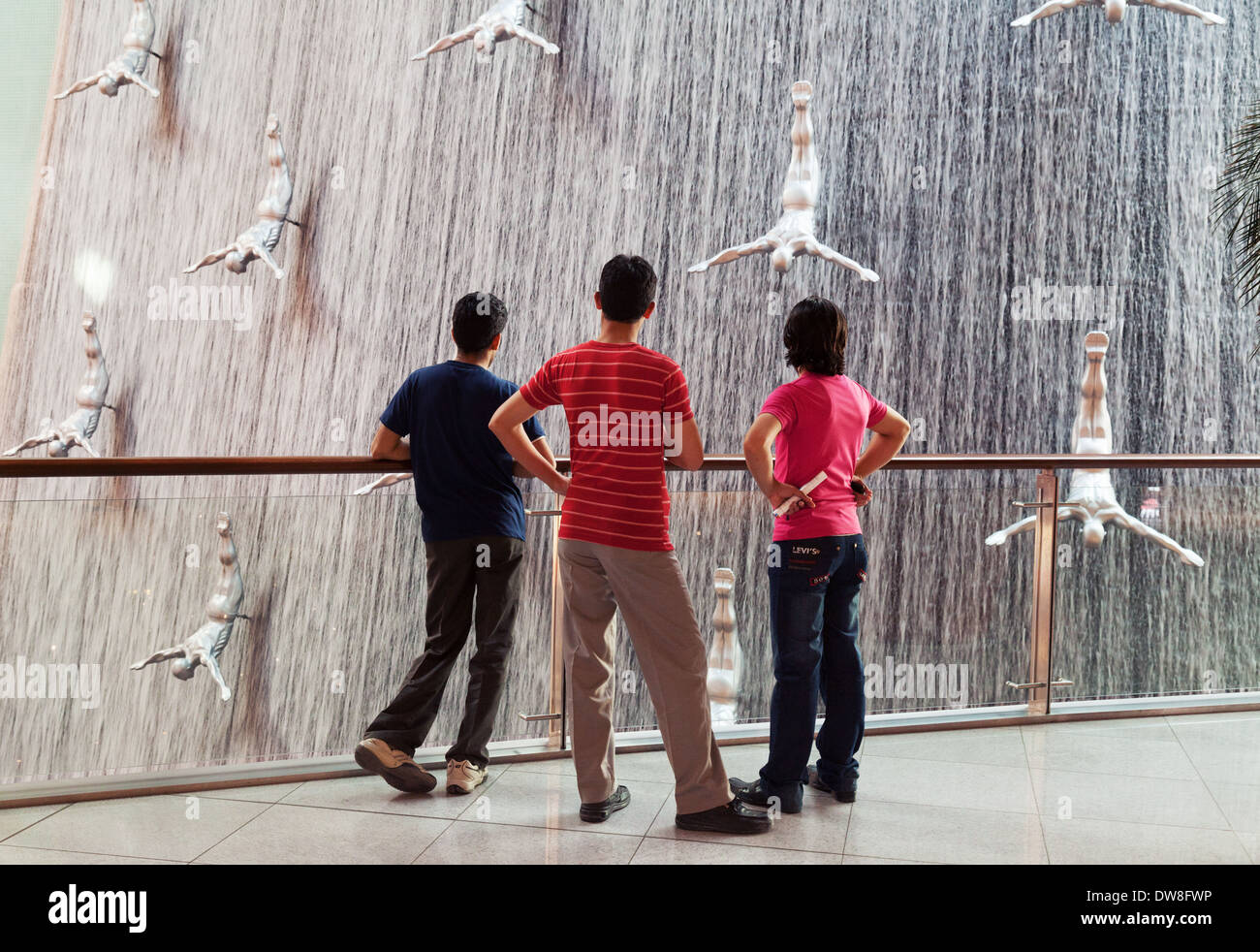 Three local teens teenage boys looking at the Waterfall in the Dubai Mall, Dubai, UAE, United Arab Emirates Middle East - Stock Image