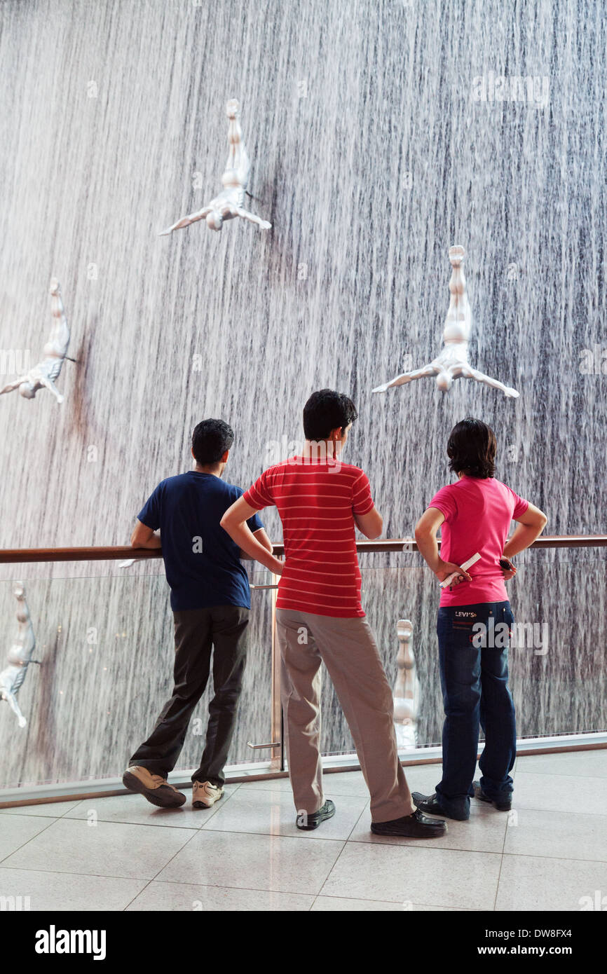 Three local teens teenage boys looking at the Waterfall in the Dubai Mall, Dubai, UAE, United Arab Emirates Middle East - Stock Image