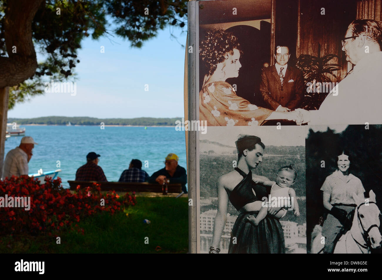 Local men take shelter from the hot sun beside old poster photographs of Marshall Tito greeting Elizabeth Taylor. Fazana. Croatia - Stock Image