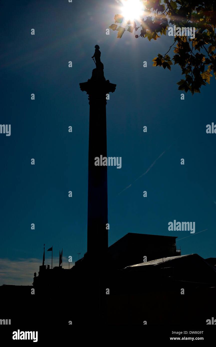 Silhouette Nelsons column Trafalgar square London blue sky sun flare in shot - Stock Image