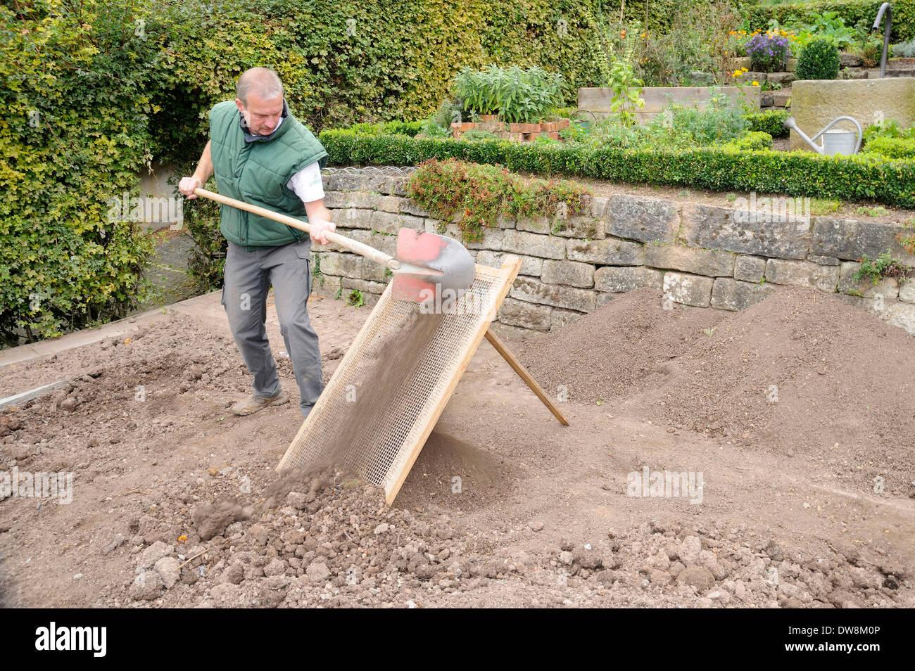 Man sifting earth - Stock Image