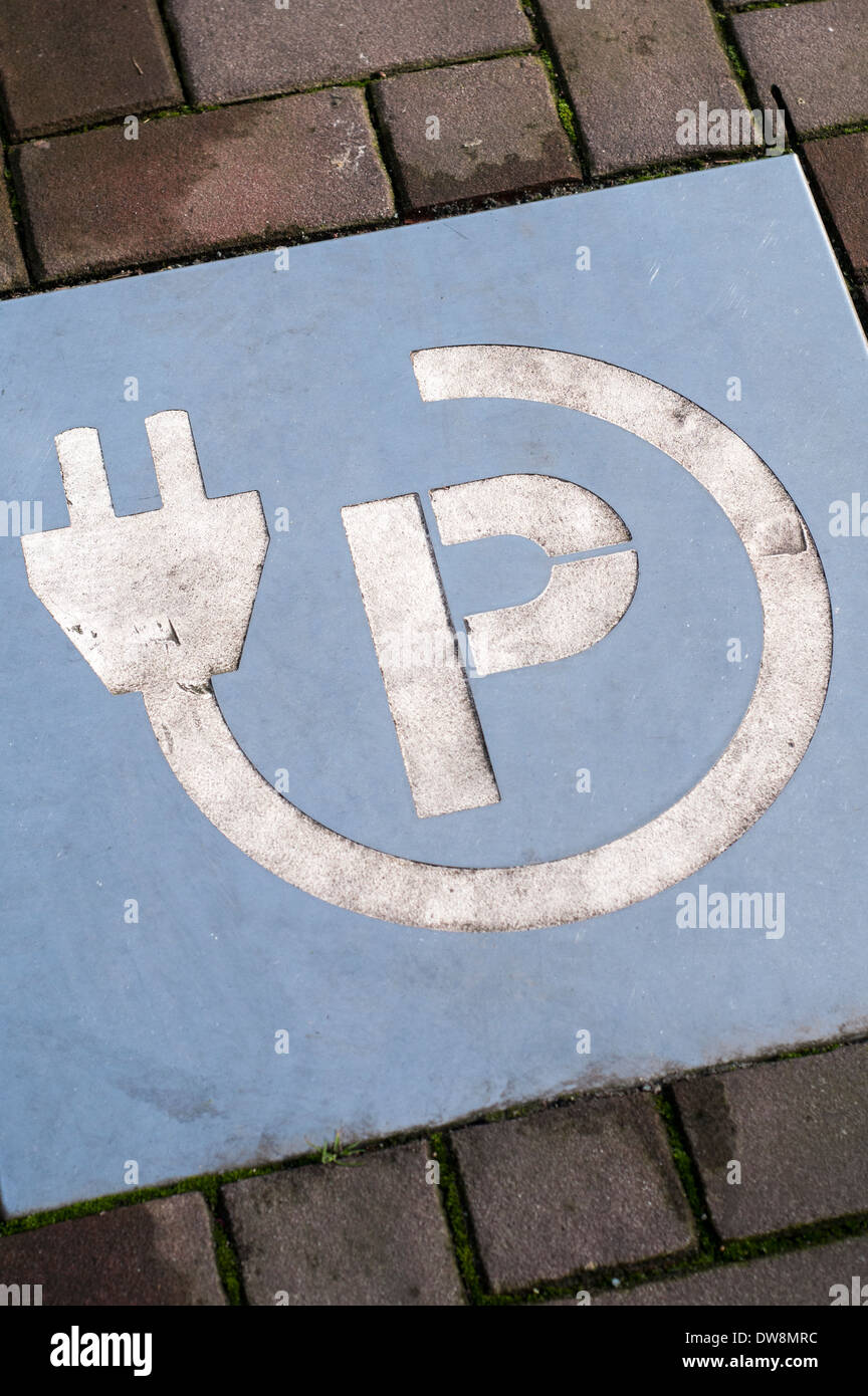 Sign on a road indicating a parking spot and charging station for an electric car or vehicle Stock Photo