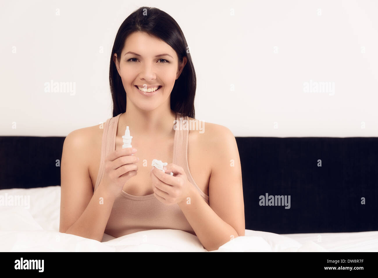 Smiling woman sitting in her bed after using nose drops to clear her congestion - Stock Image