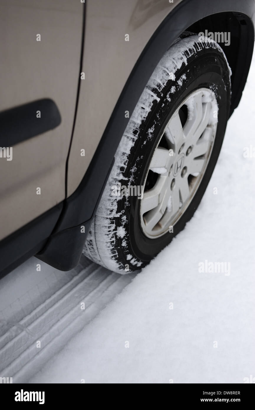 Front right wheel tire tyre in the snow on a Honda CRV small SUV all wheel drive - Stock Image