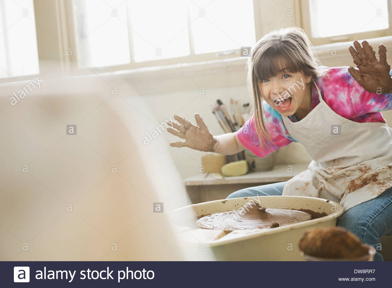 Portrait of girl showing palms in pottery class - Stock Image