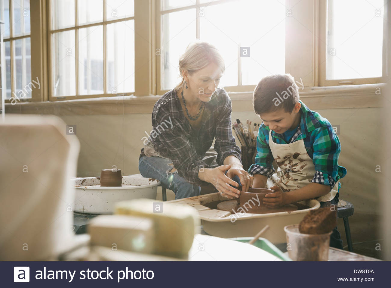 Female teacher assisting boy in pottery class - Stock Image