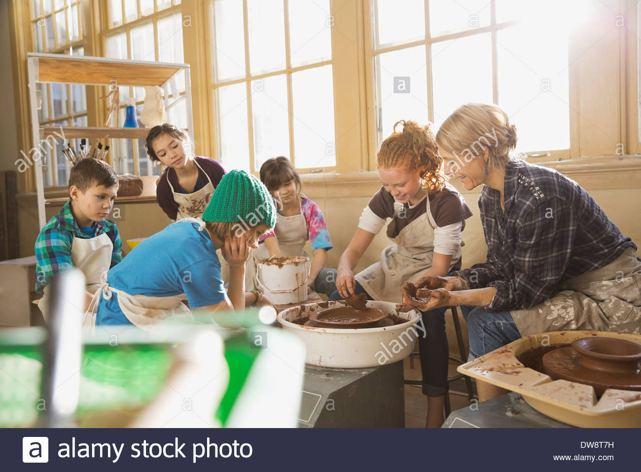 Teacher assisting students in pottery class - Stock Image
