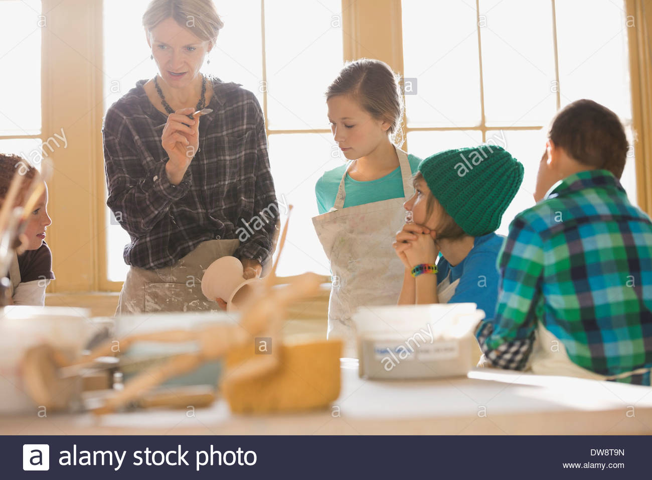 Teacher explaining glazing techniques to students in art class - Stock Image