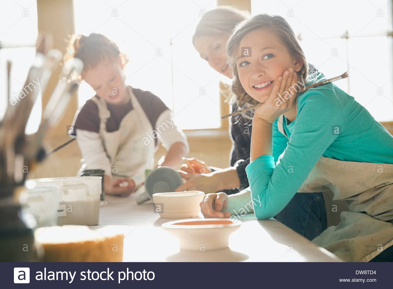 Portrait of girl sitting at table in art class - Stock Image