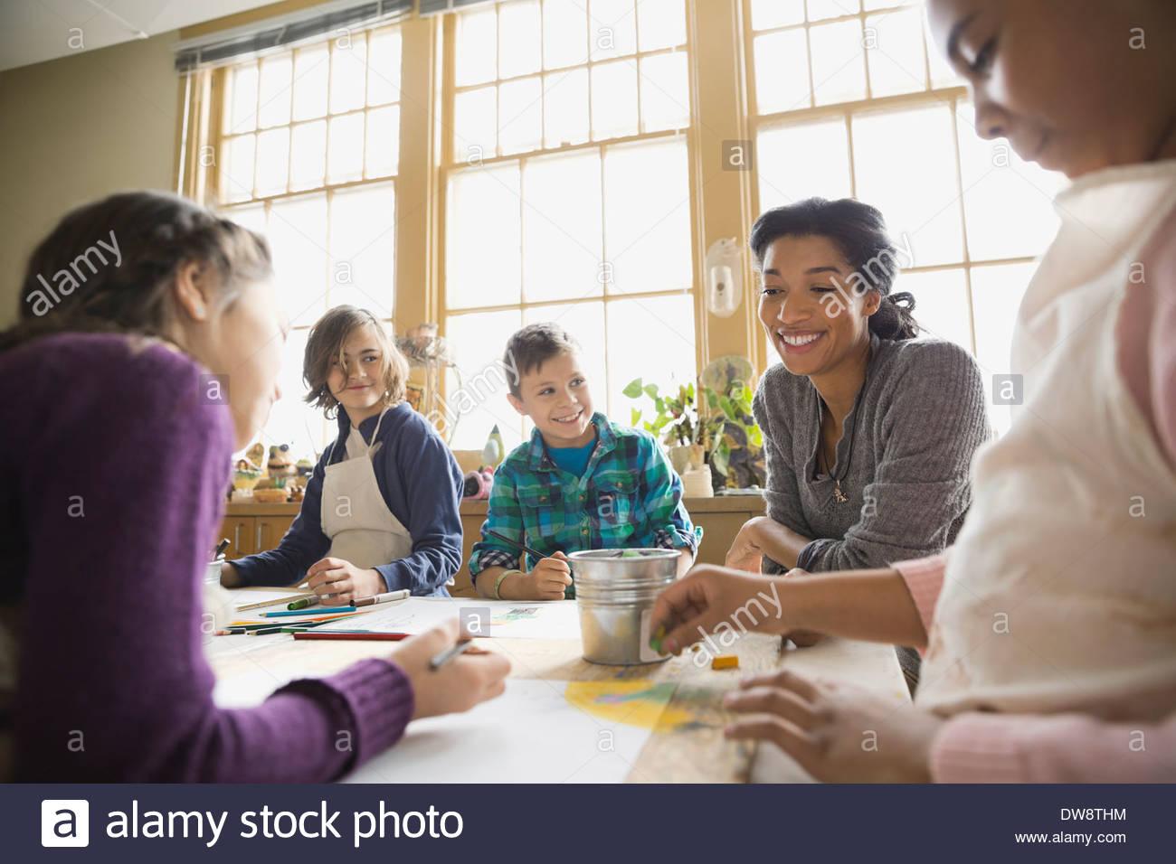 Teacher watching students in art class Stock Photo