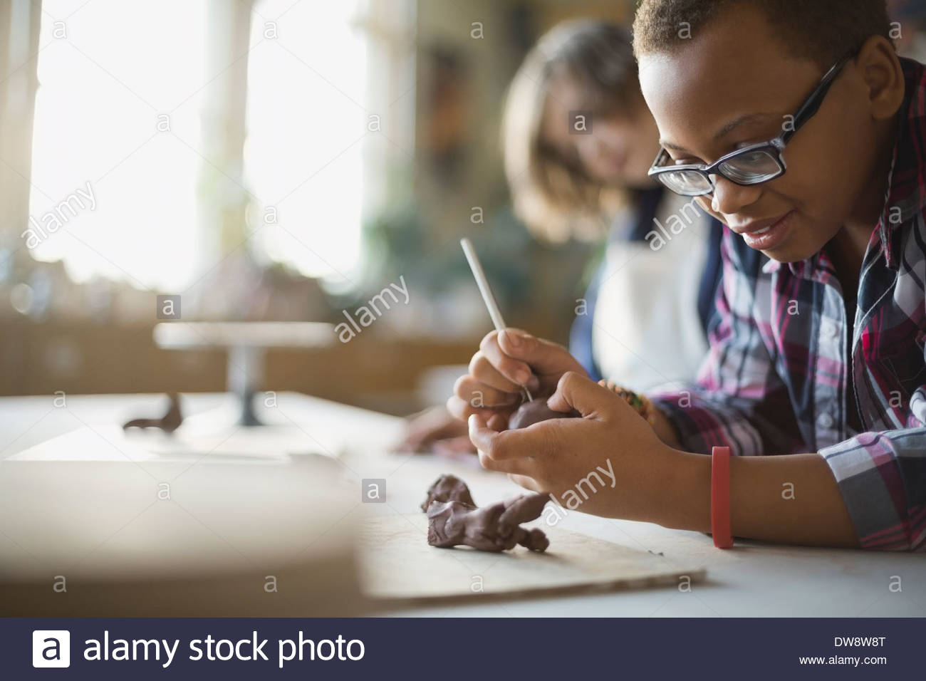 Boy creating clay figurines in art class - Stock Image