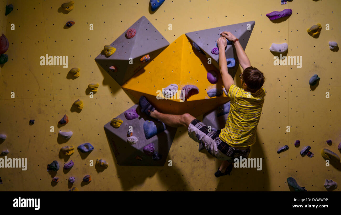 Indoor climber or boulder on the move over a formation, surrounded by many grips, left foot anchored - Stock Image