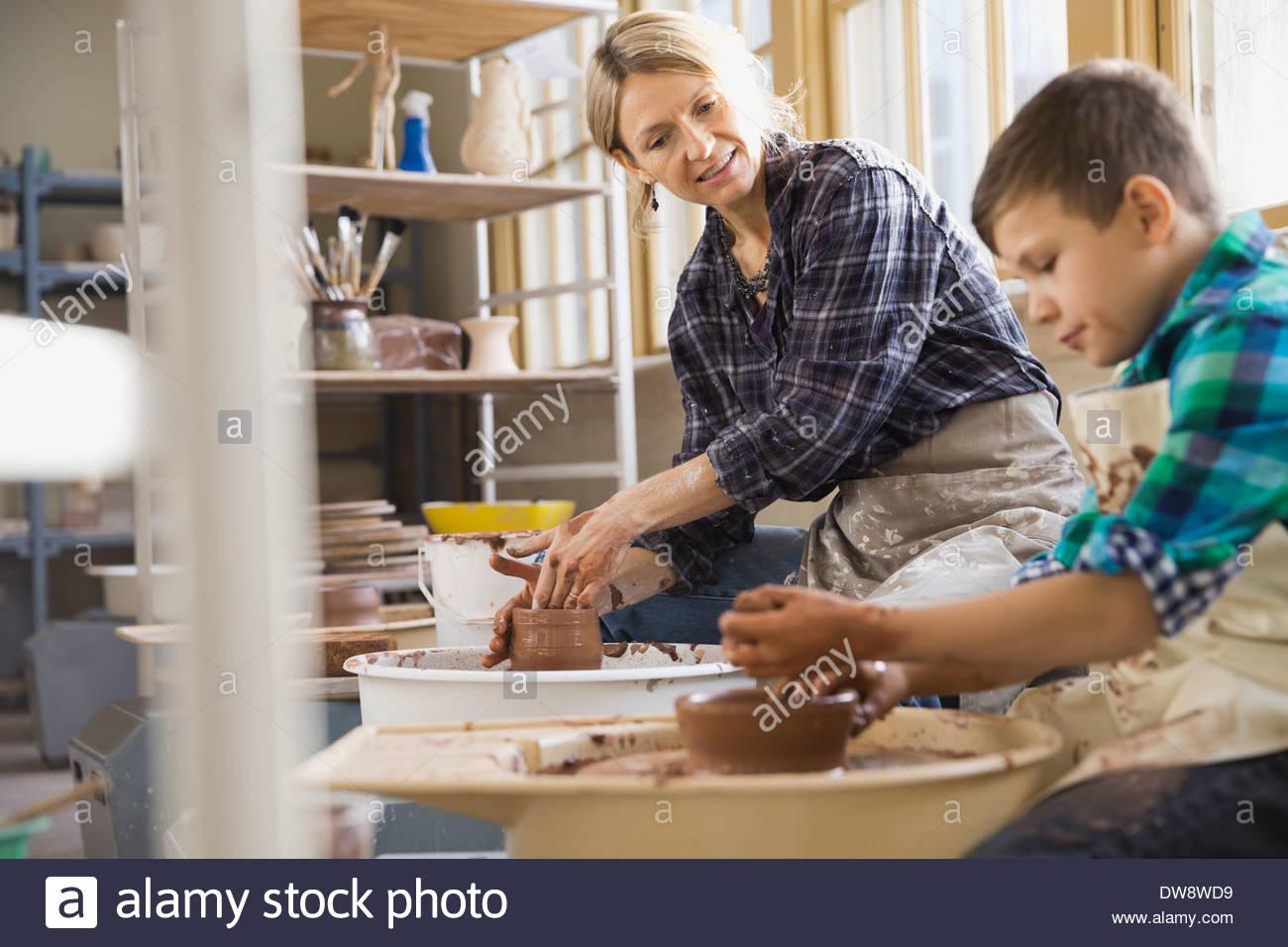 Teacher explaining boy in pottery class - Stock Image